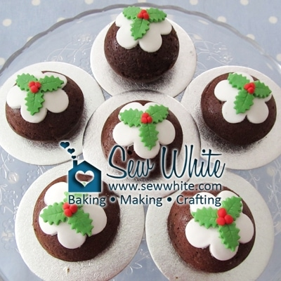 little Christmas Pudding Cakes topped with white icing and cut out holly leaves