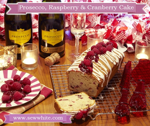 Prosecco Raspberry and Cranberry Cake drizzled with icing and topped with fruit and served with a glass of prosecco
