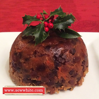 Finished traditional christmas pudding ready to be enjoyed. Decorated with a sprig of holly