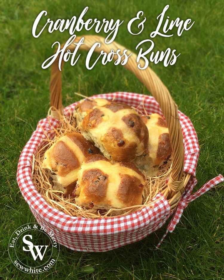 Cranberry and Lime Hot Cross Buns on a checked cloth in a wicker basket