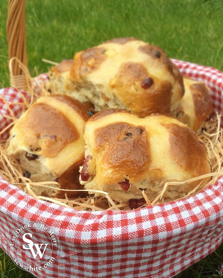 Cranberry and Lime Hot Cross Buns in a wicker basket on straw for Easter.