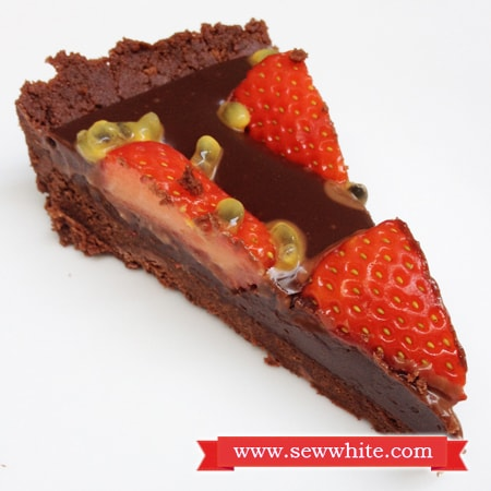 A slice of chocolate tart with strawberries and passion fruit
