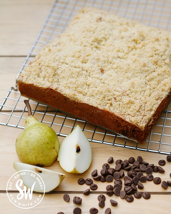 Gold brown Pear Crumble Cake with fresh pears and chocolate chips on a kitchen table