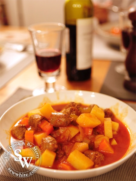 Slow Cooker Venison Sausage Stew served up ready for dinner with red wine.