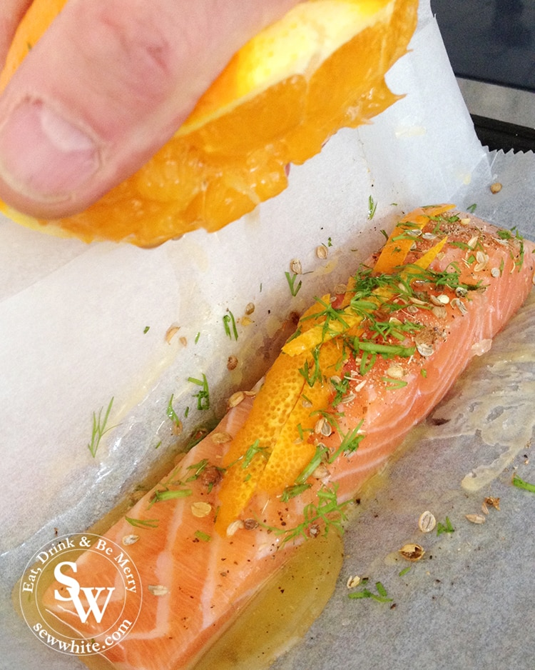 close up of the orange juice being squeezed over the salmon piece