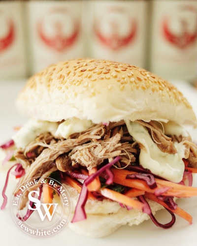 Beer Pulled Pork ready to eat served in a bun with seasame seeds and a simple slaw with red cabbage