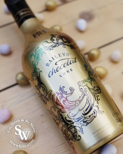 Baileys chocolat luxe in a gold bottle surrounded by mini eggs for the Chocolate Flat White Martini