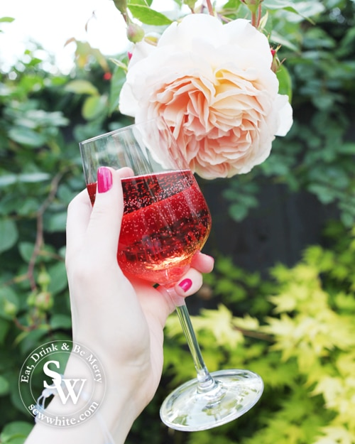 Holding a glass of rose in the garden next to a flower in the Top Rose wines for summer