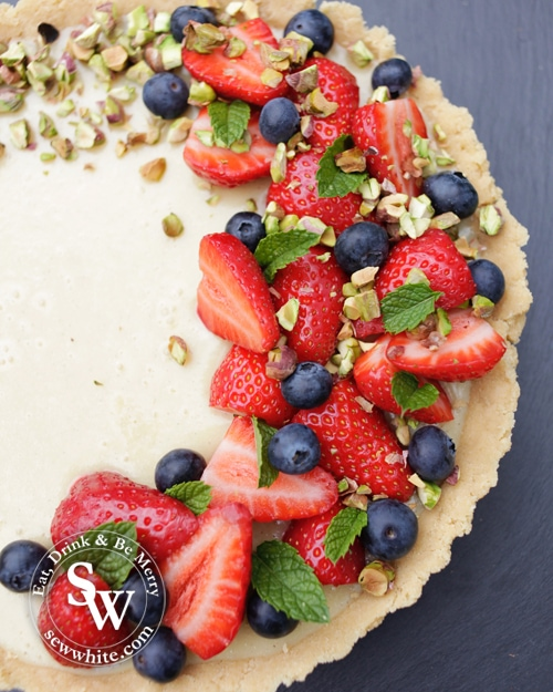 white chocolate tart deocrated with strawberries and blueberries plus pistachios