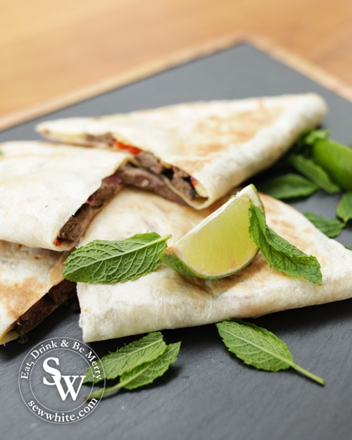 Mojito Beef Quesadillas on a slate board with fresh lime and mint