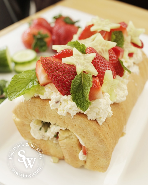 Brightly coloured Pimms Cake roulade perfect for Wimbledon. Topped with fresh strawberries