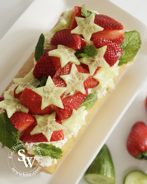 Pimms Cake topped with star shaped cucumber slices, fresh strawberries find and whipped double cream