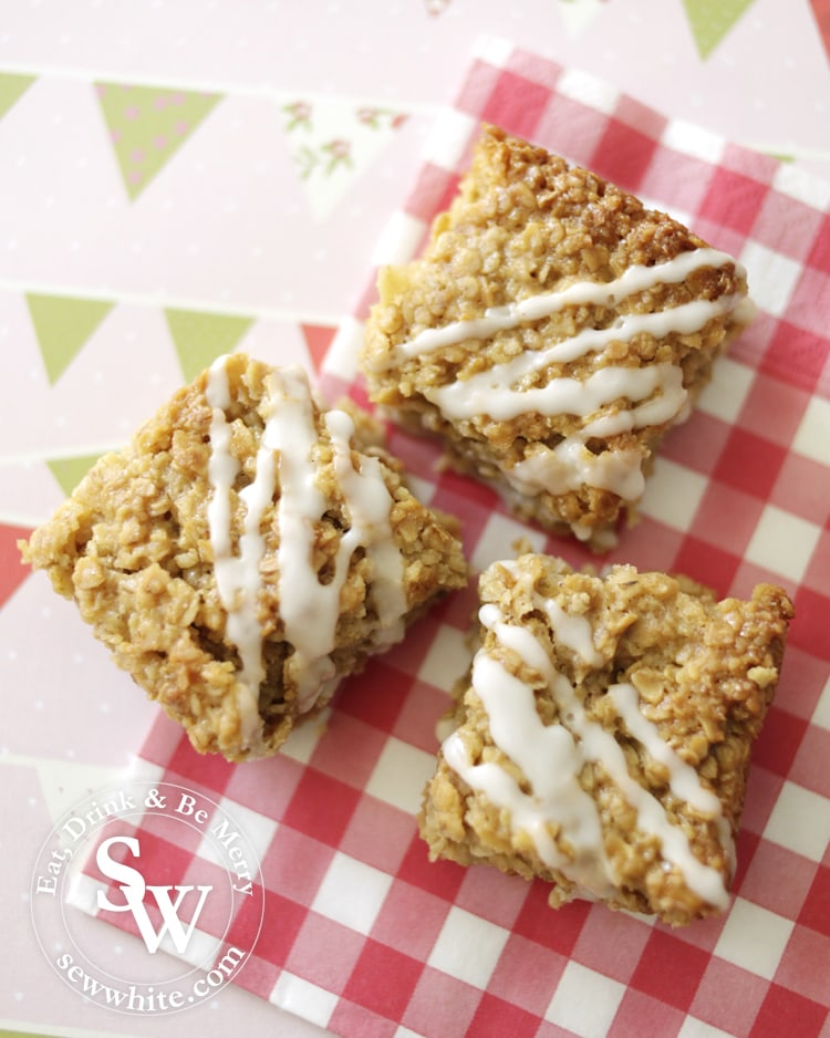 lemon and ginger flapjacks drizzled with white icing on a tartan napkin