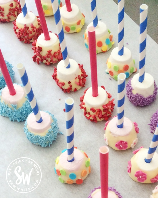 marshmallows on sticks dipped in chocolate and covered with sprinkles