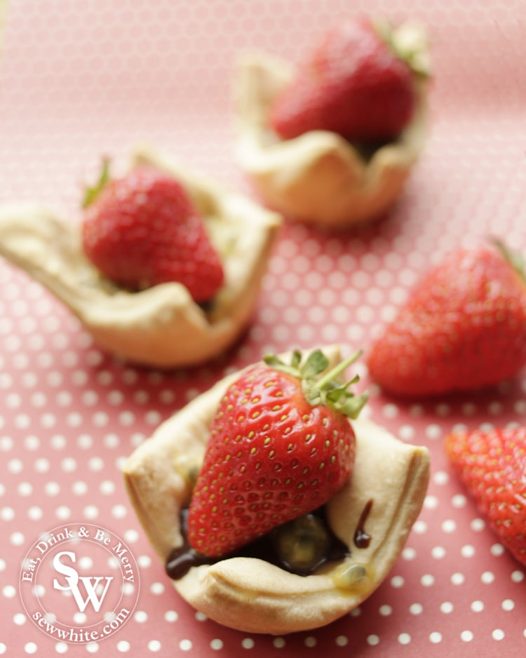 Bite-size Chocolate and Strawberry Tarts on a pink polka dot background