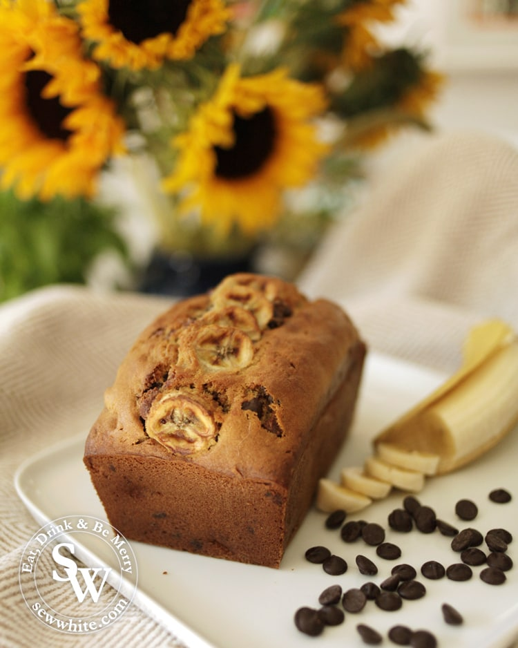 Banana Bread with Chocolate Chips on a plate with sunflowers