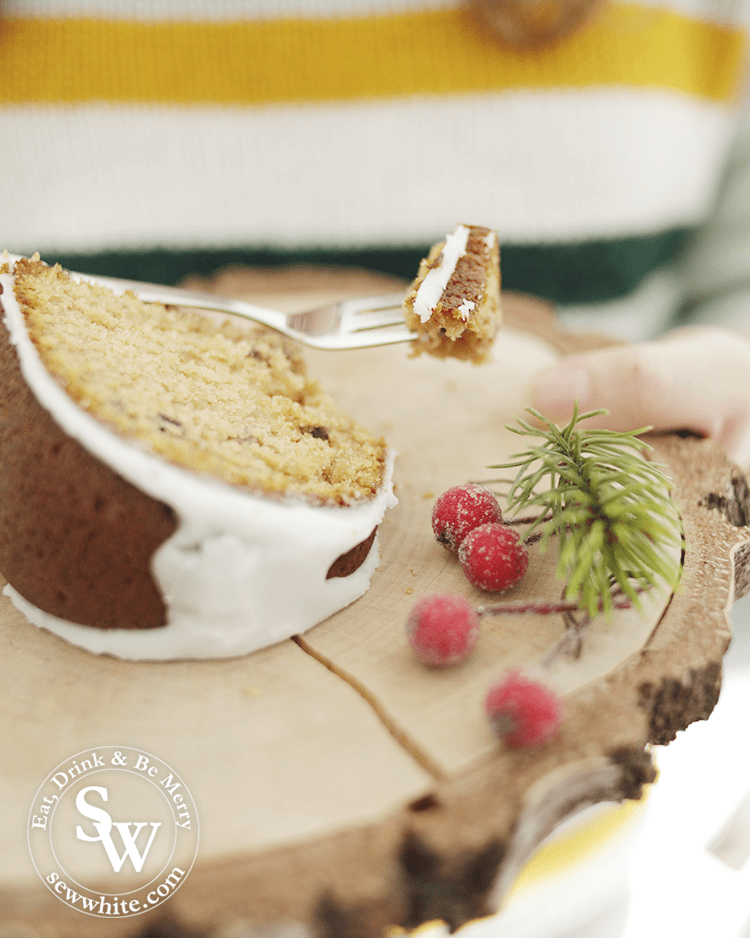 a gorgeous slice of Mince Pie Christmas Bundt Cake on a log slice plate and cake fork