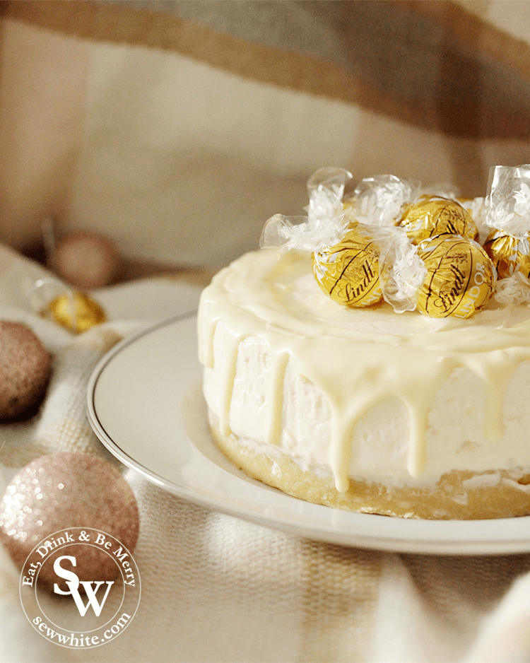 A beautfiul Baileys and White Chocolate Cheesecake decorated with drip chocolates and truffles