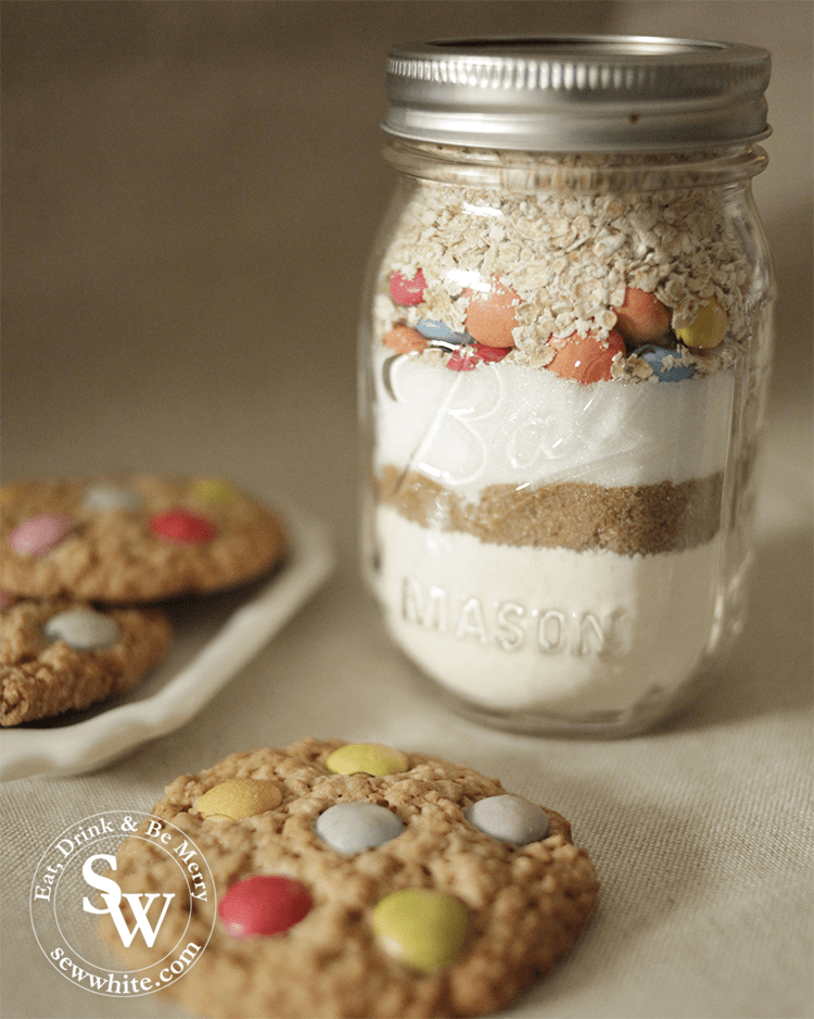 a glass jar filled with the cookie jar ingredients with smarties