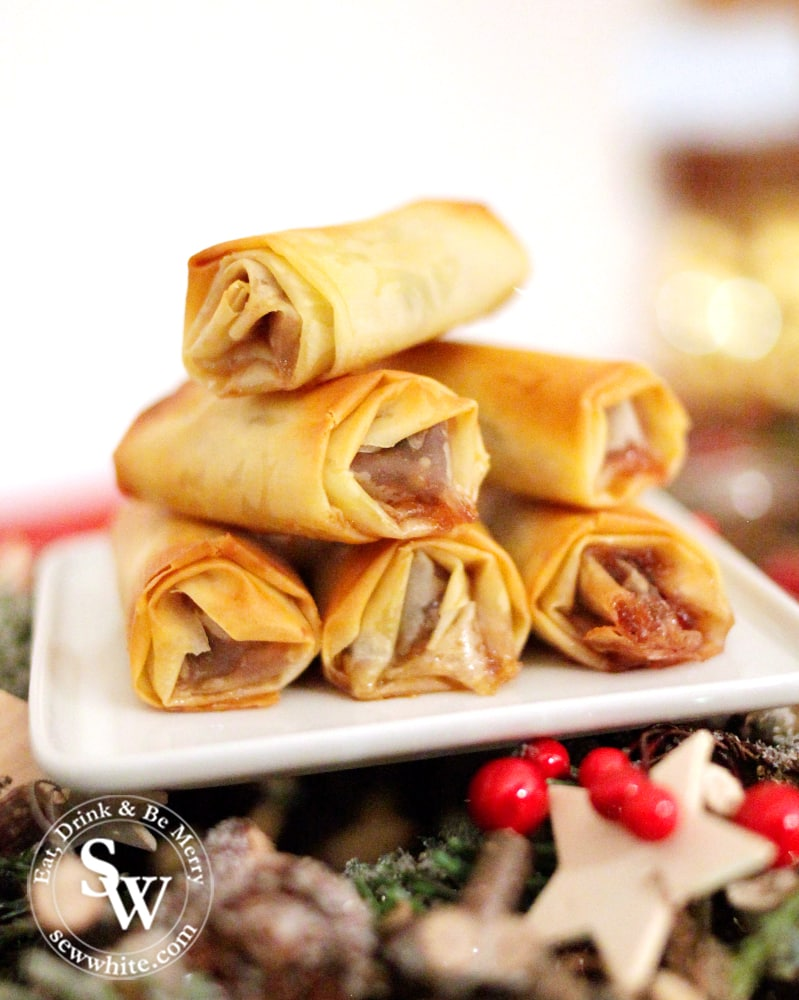 filo pastry mince pie rolls on a white plate.