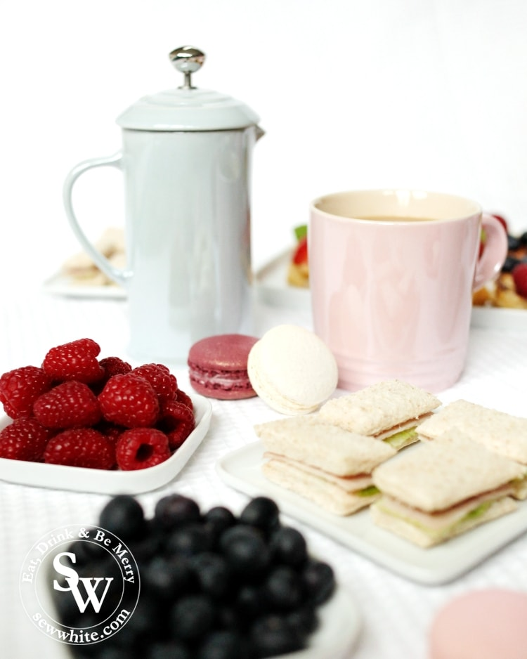 Stoneware cafetiere from Le Creuset galce collection along afternoon tea sandwiches, macarons and fruit