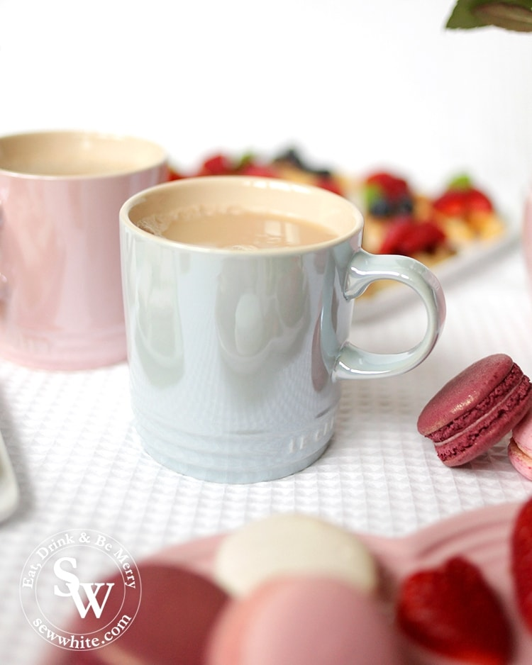 A cup of tea in the Le cureset stoneware glace collection mug served with macarons.