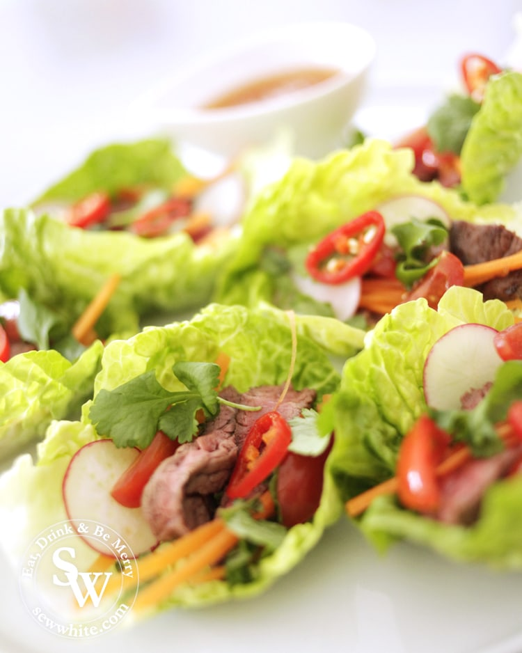 Vietnamese lettuce wraps filled with steak, raddish, chilli and carrots with spicy dipping sauce