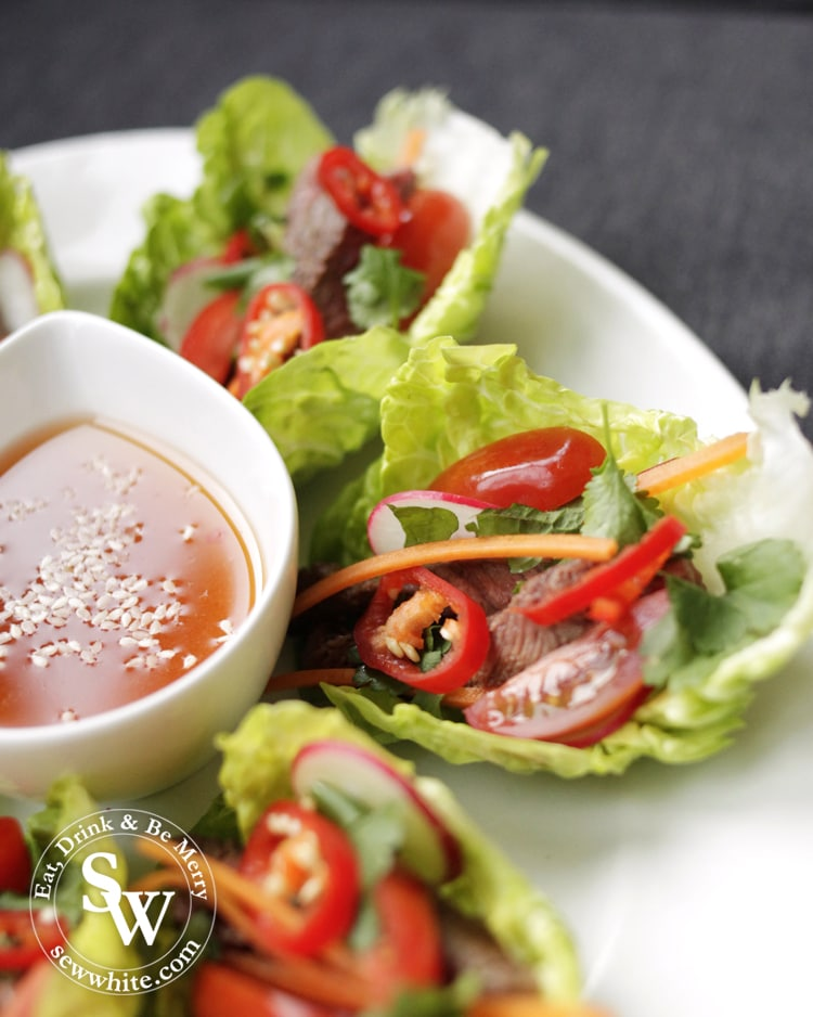 Vietnamese Inspired Beef Salad Bites serving, the bright colurs of the tomatoes, chillies, carrots and green herbs make it very appetising. With a sweet chilli dipping sauce