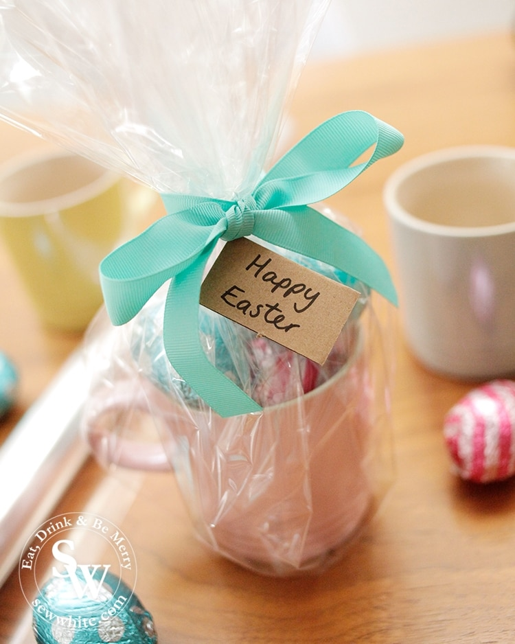 Cellophane wrapped mug with Easter eggs and a brown paper tag. Easter presents.
