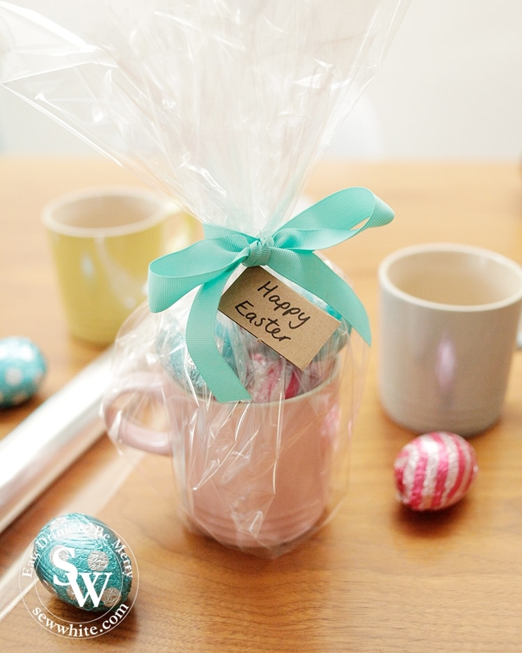 wrapping up a mug filled with easter eggs and wrapped up with clear film and a ribbon.