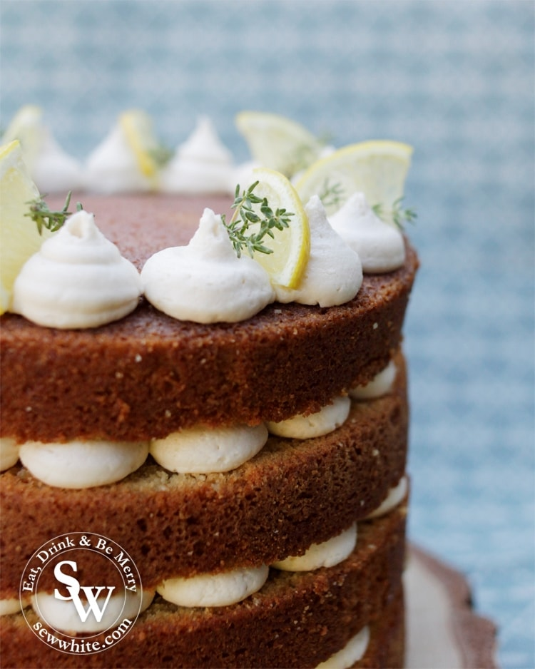 Close up view of the gin cocktail cake layers. Golden brown cake with white buttercream swirls.