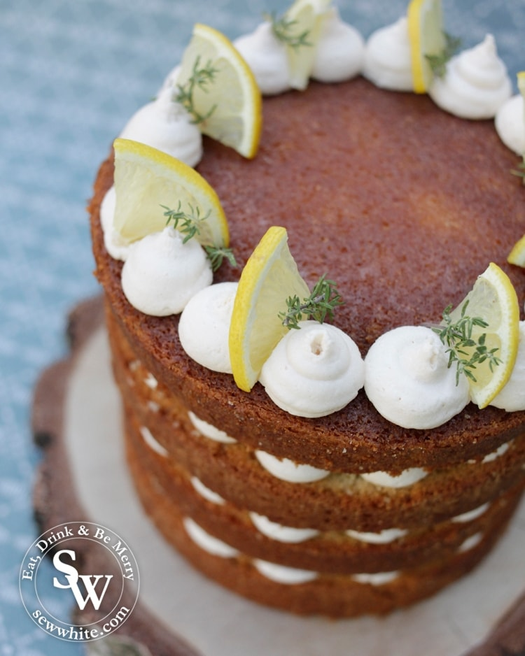 Top view of the gin layer cake which is a beautiful golden brown gin layer cake topped with white buttercream blobs along with fresh lemon slices and fresh thyme.