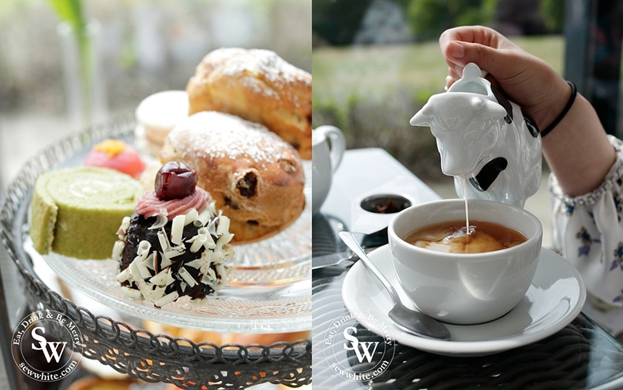 A cow shaped milk jug perfect for afternoon tea along side a range of delicious sweet patisserie pieces.