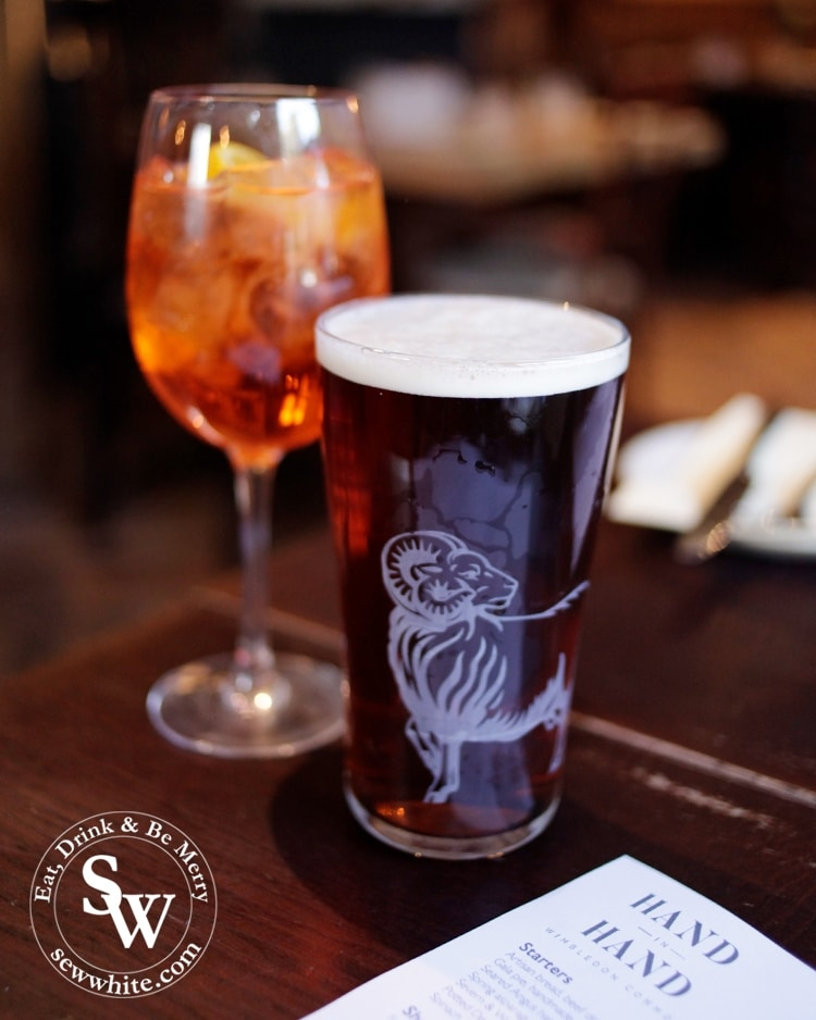 A youngs brewery ram on a glass at The Hand in Hand in Wimbledon Village with an Aperol Spritz in the background.