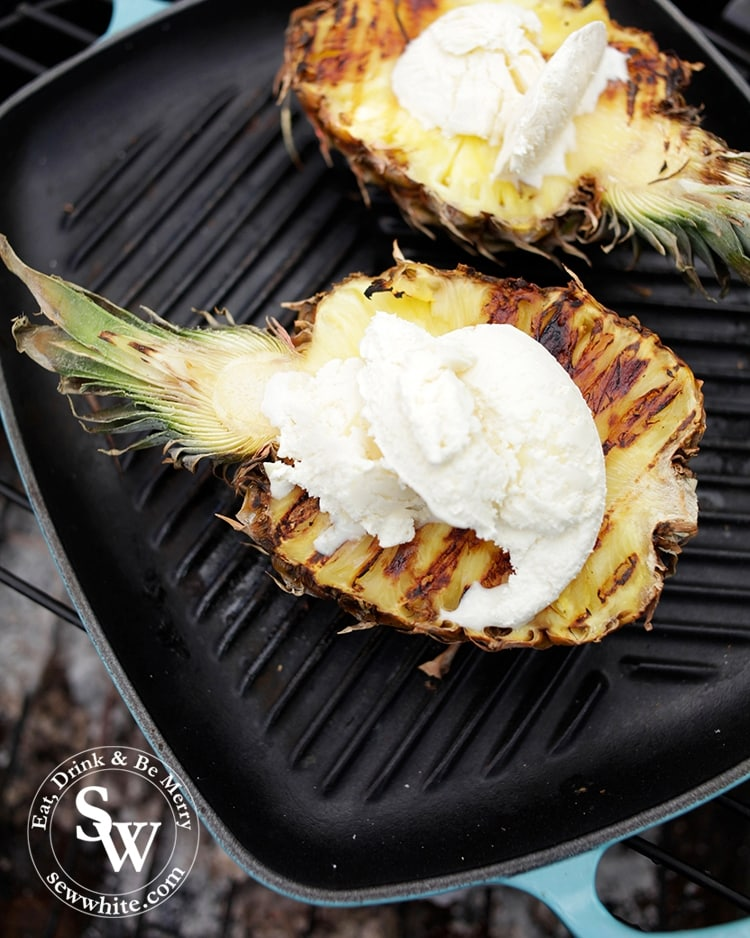 BBQ Grilled Pineapple served on the teal Le Creuset grill pan on the camp fire with white chocolate ice cream on top.