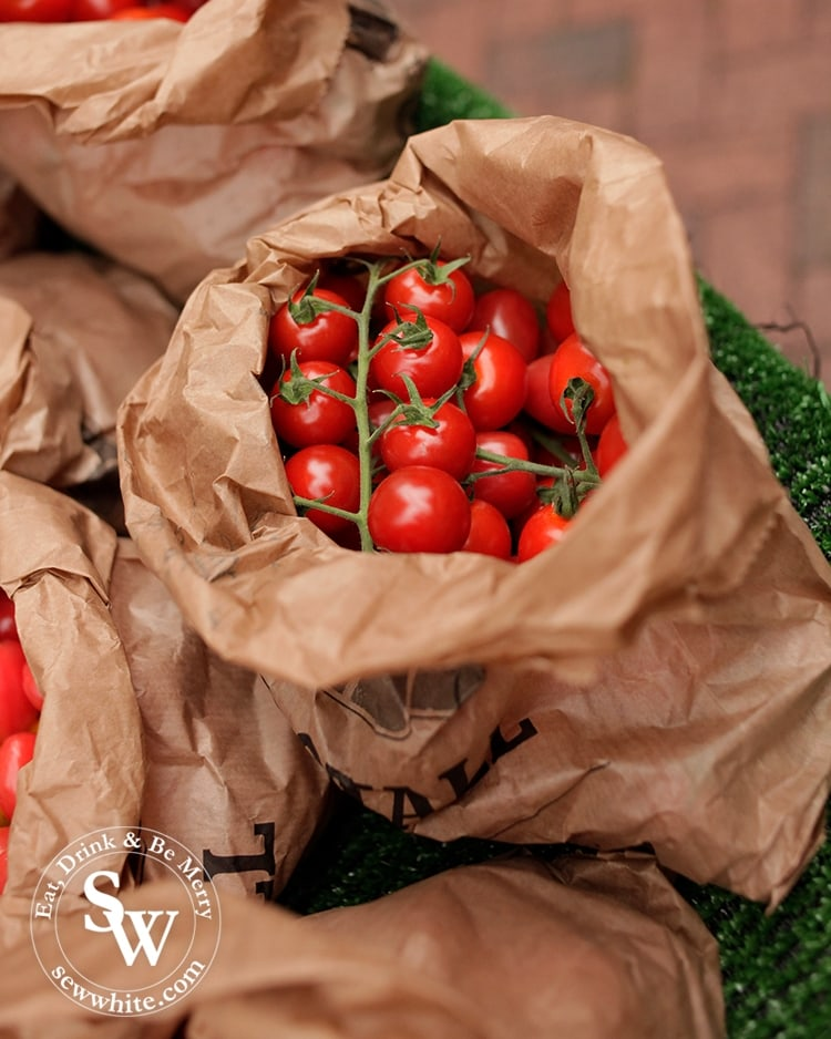 A brown paper over flowing with vine ripened tomatoes at Wimbledon Village Farmers' Market.