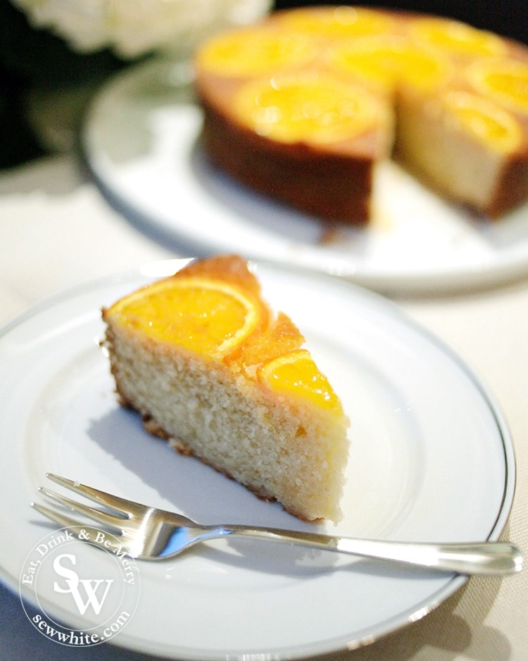A golden orange sponge slice ready to enjoy with silver pudding fork decorated with slices of orange.
