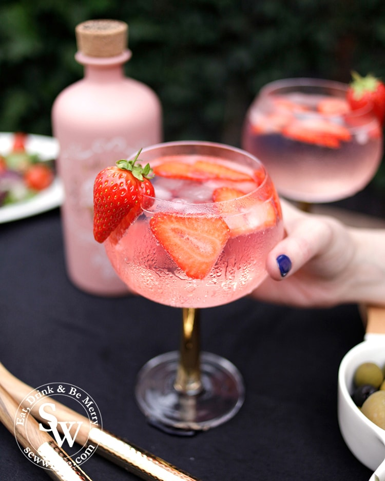 Hand holding the strawberry gin and tonic. Condensation on the glass and a strawberry as decoration.