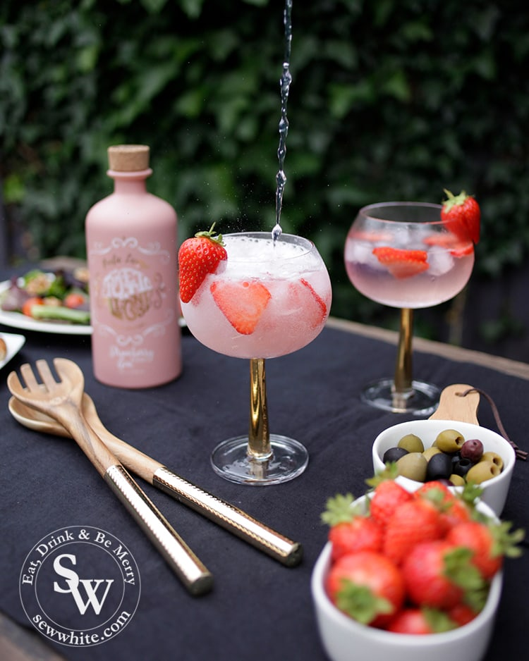 Tonic water being poured into a strawberry gin and tonic on a blue table.