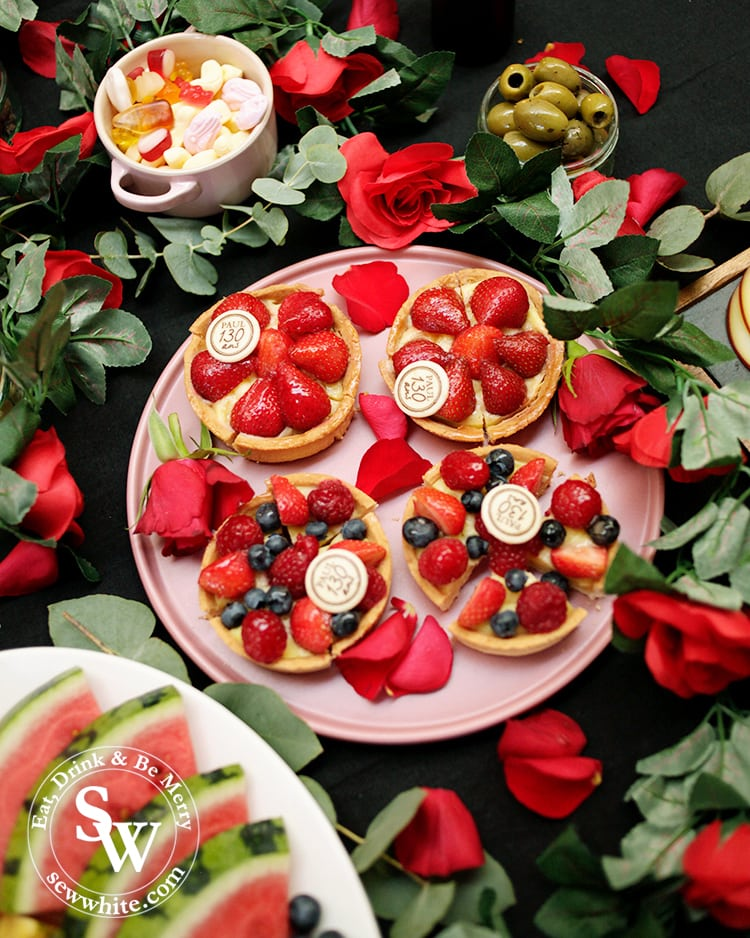 Beauty and the Beast Party table ideas. A dark tablecloth covered in Paul bakery strawberry tarts studded with berries. The plate wrapped in a rose garland and covered in rose petals.