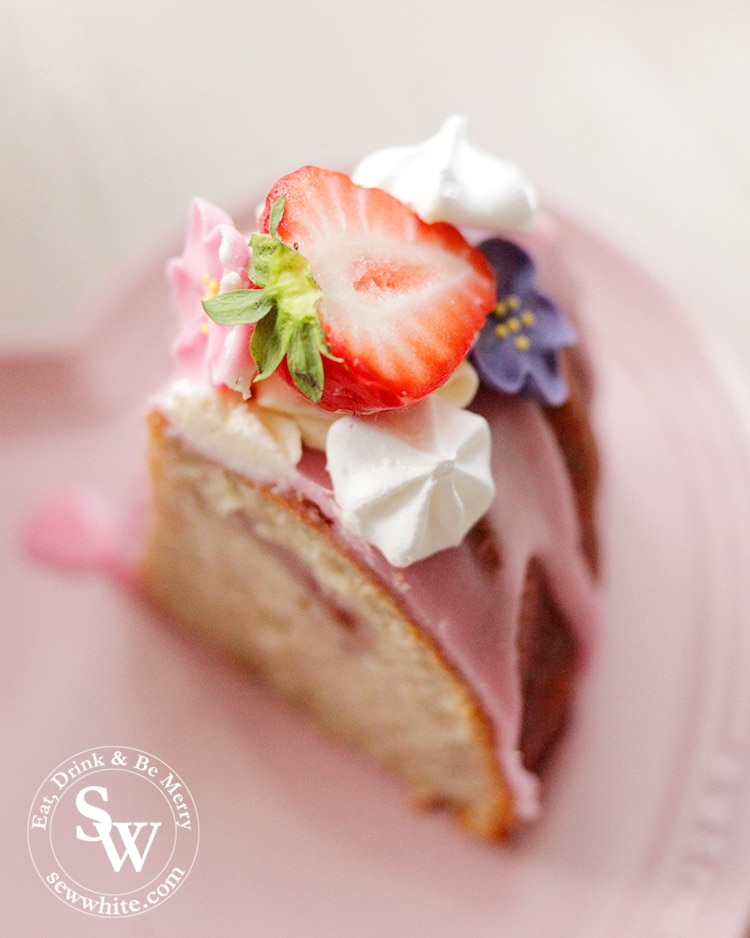 A beautiful slice of Strawberry Prosecco Cake topped with pink icing, meringues and sugar flowers.