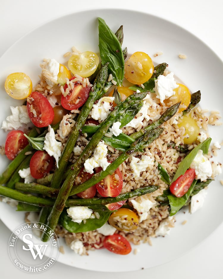 Asparagus placed on top of a bed of rice, mozzarella and tomatoes.