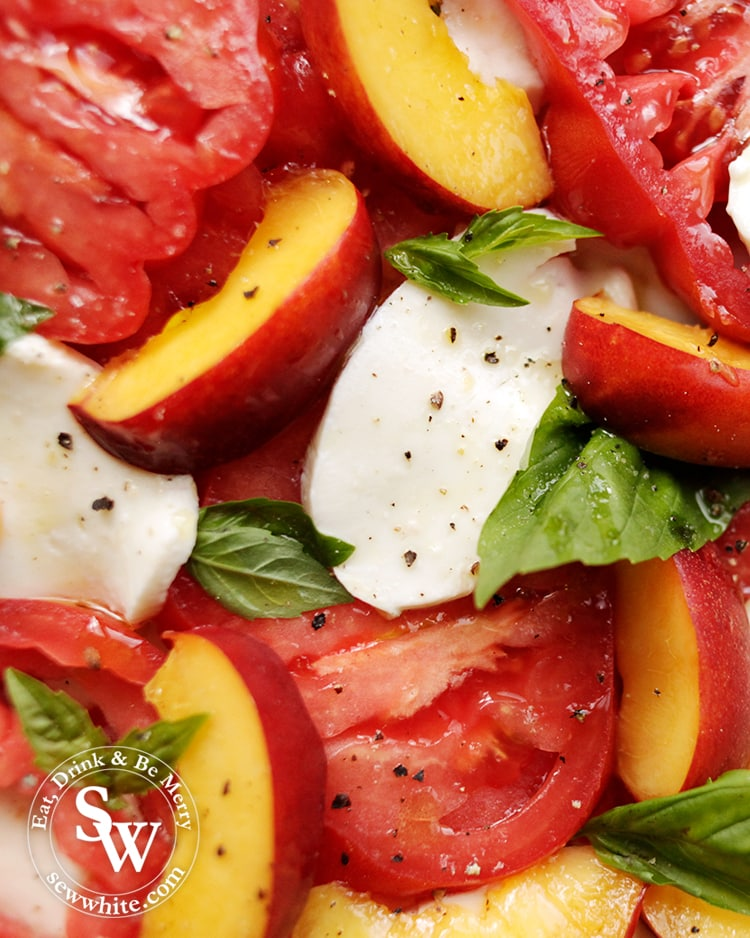 A close up of Heirloom Tomato and Peach Salad with large slices of mozzarella, cracked black pepper and fresh basil. Drizzled with olive oil.