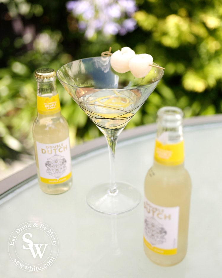 Lemon Lychee Martini in a large martini glass decorated with lychees and pictured with Double Doutch premium mixers.