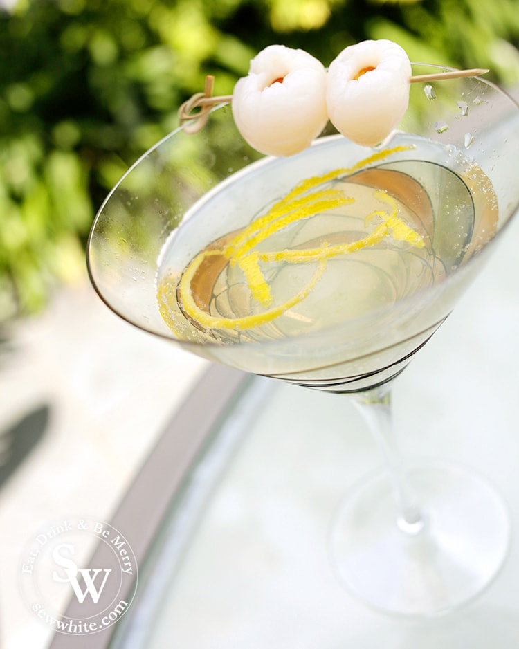 Freshly served up Lemon Lychee Martini in a large glass martini glass with strips of lemon inside and decorated with lychees.