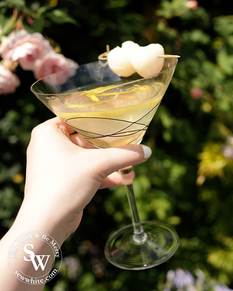 Cheers to a beautiful cocktail. Large cocktail glass being held against roses with lychees in it.