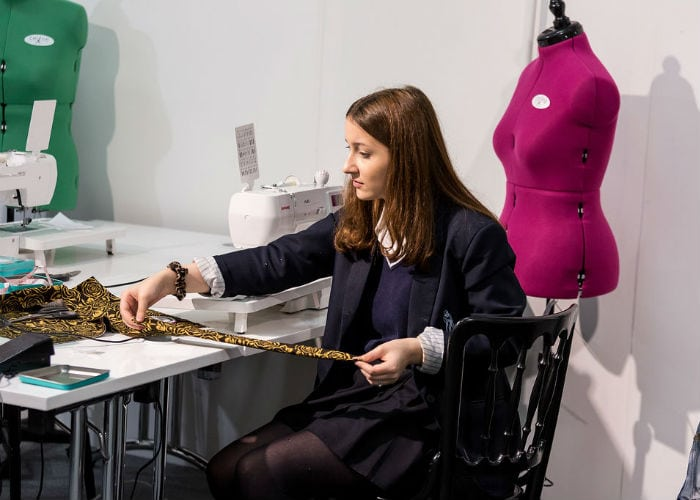 Young girl at a sewing machine at the Workshops at the Knitting and Stitching Show Alexandra Palace October