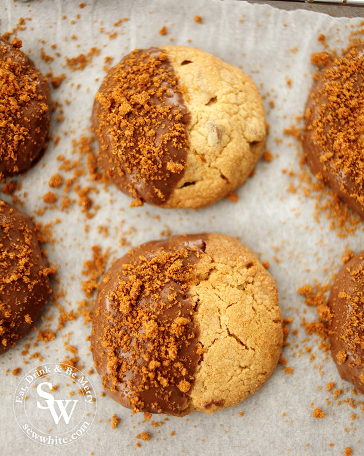 Gorgeous Biscoff Chocolate Chip Cookies with biscoff biscuit crumbs on greaseproof paper