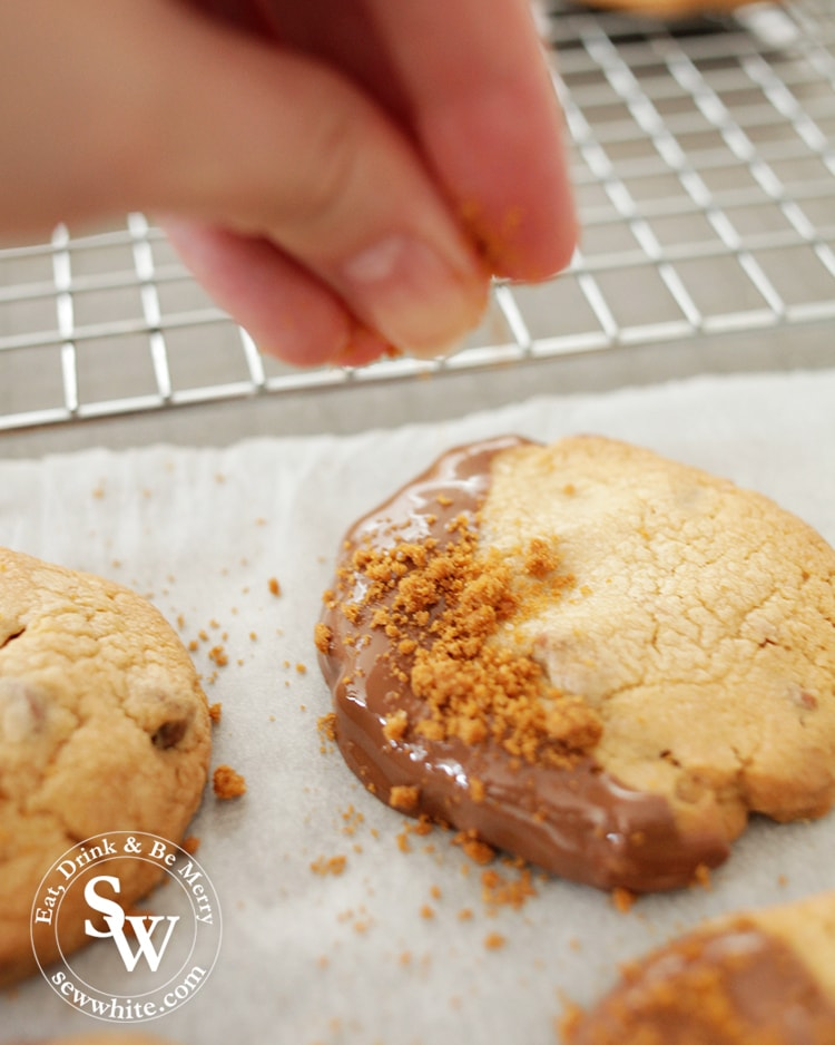A hand dusting the biscoff crumbs on to the chocolate cookies