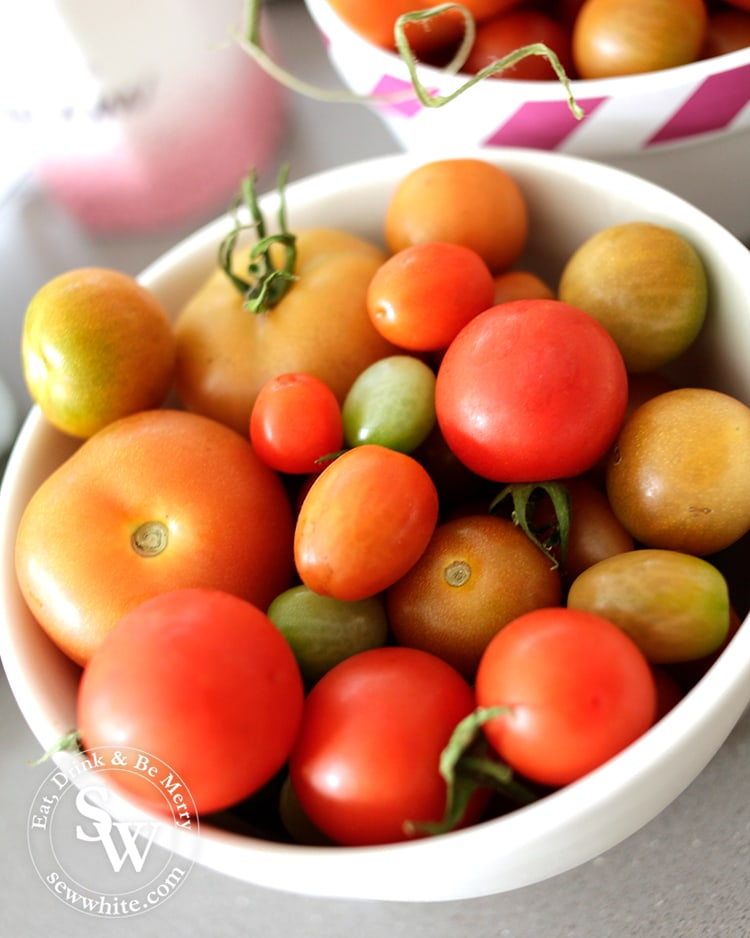 Fresh home grown tomatoes of different sizes in a china bowl.